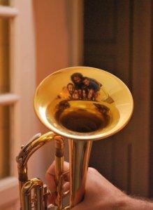 Siete en orquesta reflejados en una trompeta